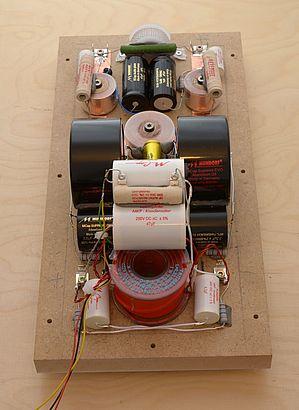 Eine Frequenzweiche mit vielen hochwertigen Bauteilen auf der Innenseite des Deckels montiert